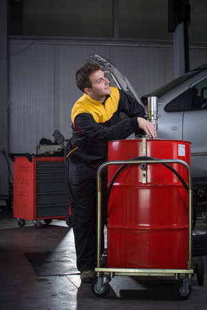is based: Portrait of handsome mechanic based on car in auto repair shop smiling Stock Photo