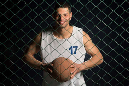 chain linked: A young basketball player gripping the ball tightly as viewed through the chain linked fence.