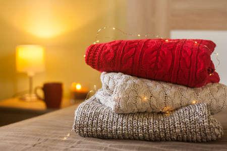 Pile de pulls tricotés sur un lit décoré de lumières. Petite lampe, bougie et tasse sur la table en bois en arrière-plan. Concept chaleureux et cosy.