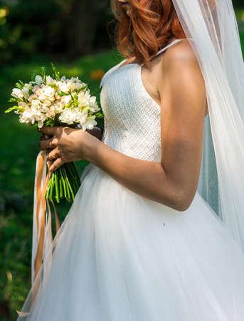Wedding elegant bouquet in brides hands. Vivid green bakground. 版權商用圖片