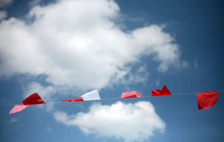 Colorful flags of the street festival, fair or party against blue sky and white clouds. Minimalistic composition. Stockfoto