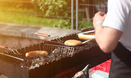 Man cooks sausages and buns for hot dogs and burgers on the grill outdoors in the summer Stock Photo