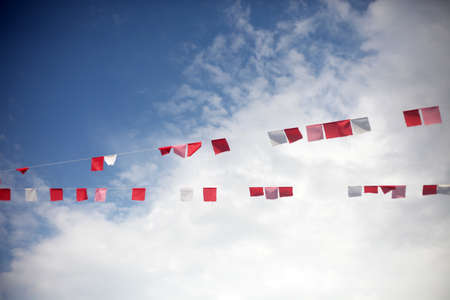 Colorful flags against blue sky with white clouds. Summer celebration, party or festival concept.