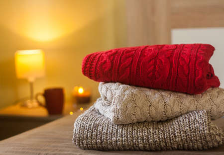 Stack of knitted sweaters on a bed decorated with lights. Small lamp, candle and cup on the wooden table in the background. Warm cozy concept. Reklamní fotografie