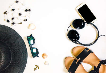 Travel female accessories phone, earphones, sunglasses, sandals, necklace and hat on white background for summer holiday and vacation concept. Reklamní fotografie