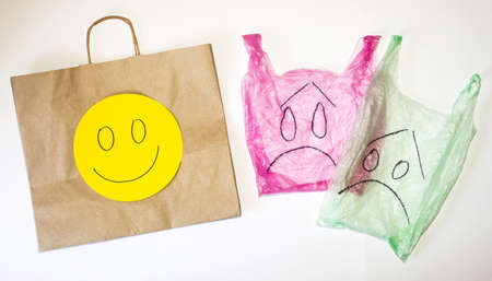 Plastic and paper bags with happy and sad emotions on faces against white background. Environment issue and plastic refusal concept. Banque d'images