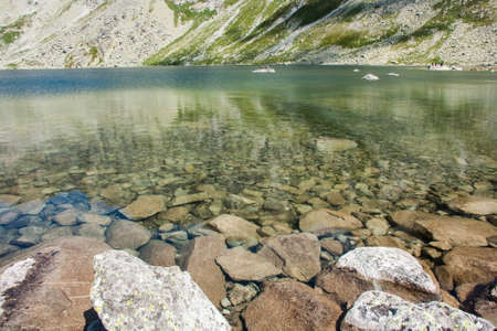 View of beautiful lake with clean water and rocks in the mountains Imagens