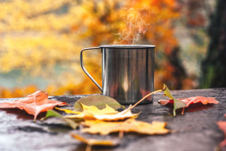 Hot drink in the steel cup on the wooden table. Autumn orange leaves. Yellow trees and lake in the background.