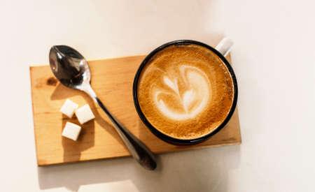 Taza de café con leche con espuma de arriba, cuchara y azúcar sobre fondo blanco. Día soleado. Foto de archivo