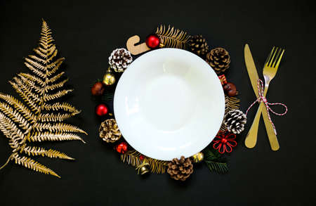 Chirstmas wreath decoration, empty white plate. Golden natural fern leaf. Flat lay, top view. Black background. Copy space.