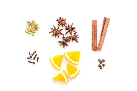 Mulled wine ingredients flat lay. Cinnamon, orange, cardamom, clove, anise and red wine on white background. Composition of traditional winter drink. Zdjęcie Seryjne