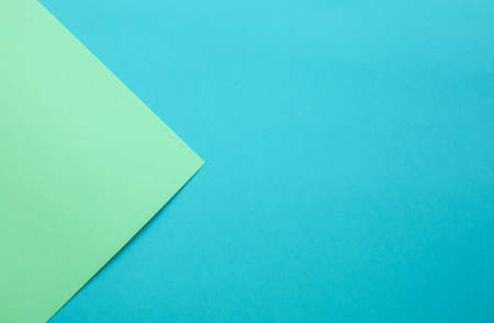 Multicolor paper diagonal background with arrow of trendy mint and blue colors. Top view, copy space.