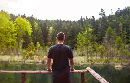 Man alone standing and looking on the desolate lake in forest. Concept of travel, psychology, mindfulness. Reklamní fotografie