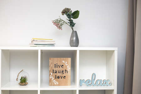 Stylish bookshelf with decorations, flowers for home on a white wall, modern interior design details