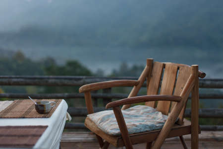 fresh air: A hot cup of coffee on wood table and fresh air in the morning