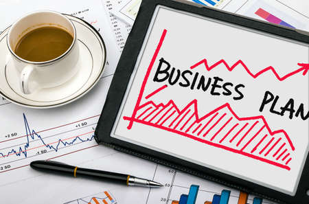 business project: business plan with financial chart hand-drawn on tablet pc