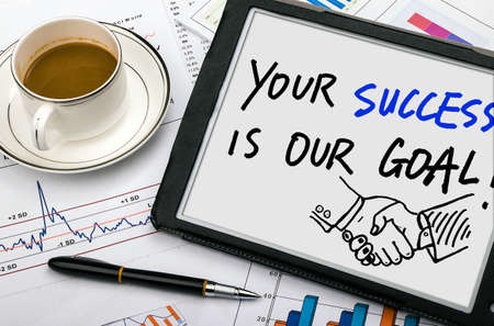 financial goals: your success is our goal handwritten on tablet pc Stock Photo