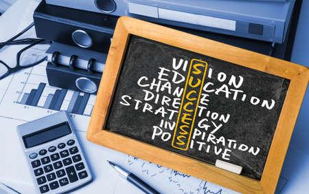 business and commerce: success crossword concept handwritten on blackboard