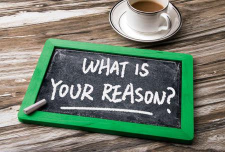 reason: what is your reason handwritten on blackboard Stock Photo