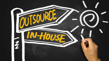 outsource: outsource or in-house signpost concept hand drawing on blackboard
