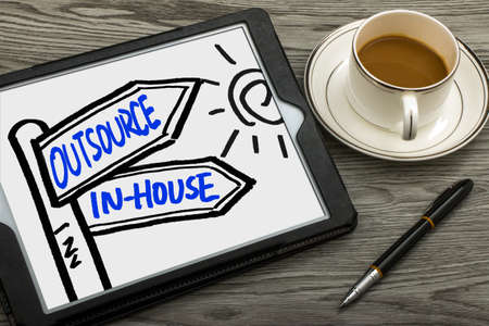 outsource: outsource or in-house signpost concept hand drawing on tablet pc