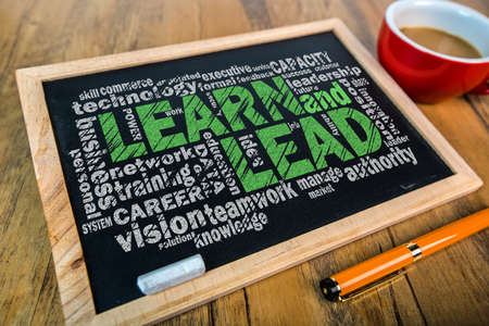 business strategy: learn and lead word cloud on small blackboard