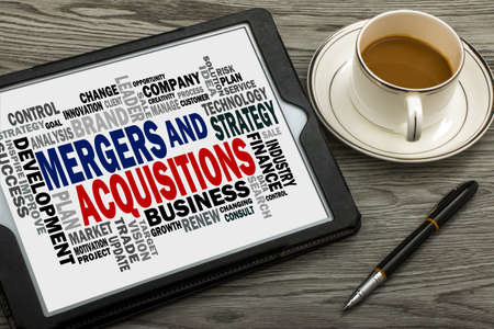 mergers: mergers and acquisitions concept with business word cloud handwritten on tablet pc Stock Photo