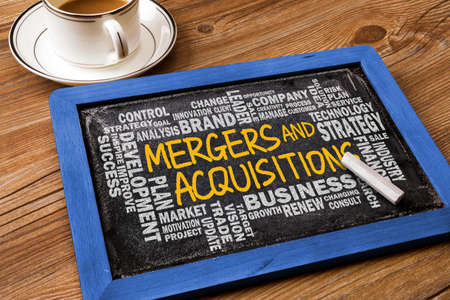 acquisitions: mergers and acquisitions concept with business word cloud handwritten on blackboard