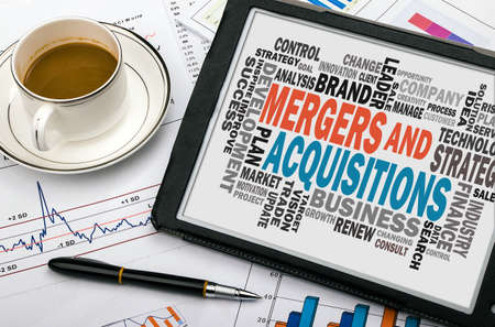 mergers and acquisitions concept with business word cloud handwritten on tablet pc Standard-Bild