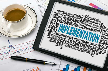 implementation: implementation concept with business word cloud on tablet pc