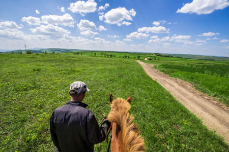 herdsman: Chinese herdsman and brown horse on grassland Stock Photo