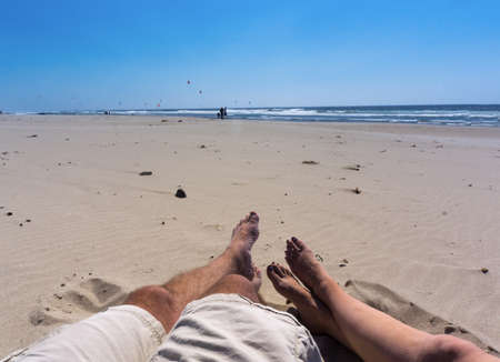 thier: Two people relaxing on the beach with thier feet in the sand watching wind surfers.
