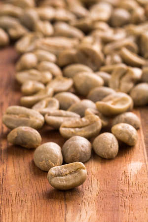 unroasted: Unroasted green coffee beans placed on a wooden cutting board.