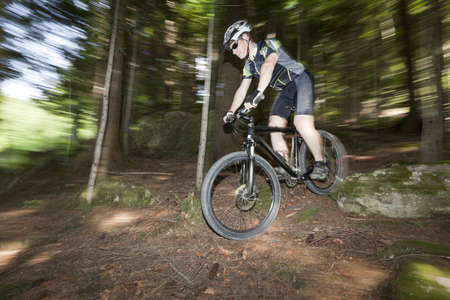 A mountain Biker in a forest. Panning the camera, so background is with motion blur. photo