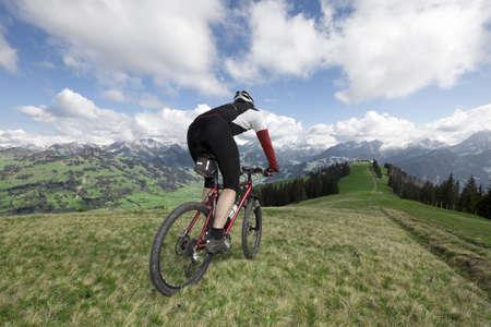en mont�e: Un m�le mountainbiker sur une prairie alpine avec fantastique vue panoramique sur les Alpes suisses.