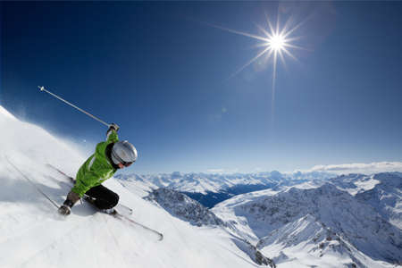 Female skier on downhill race with sun and mountain view. Stock Photo