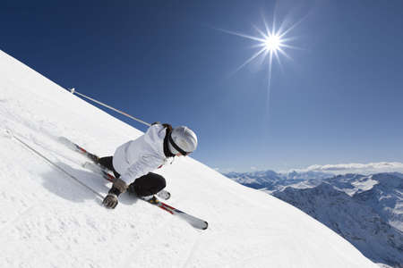 steep: Female skier on a steep slope with mountainraing and sun in the background Stock Photo