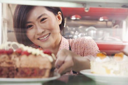 Chinese woman removing pie from display case LANG_EVOIMAGES