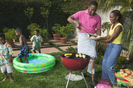 Mid adult couple having a barbeque with children playing in the background