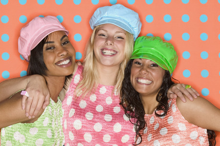 Three young women holding each other smiling looking at camera LANG_EVOIMAGES
