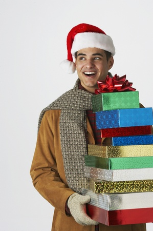 Young man holding holiday gifts LANG_EVOIMAGES