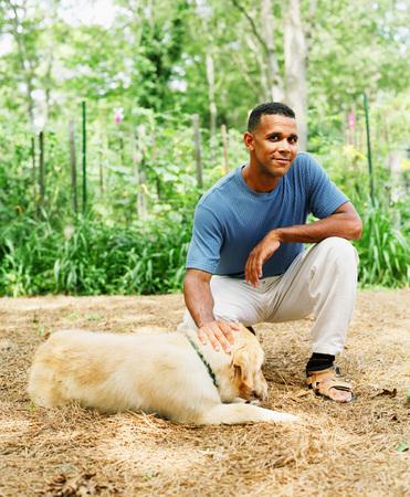 Portrait of a mid adult man petting a pet dog