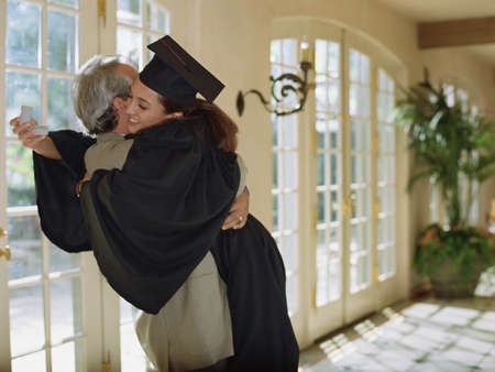 Young female graduate hugging an elderly man LANG_EVOIMAGES