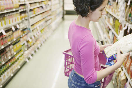Young woman holding a shopping basket and reading her shopping list at a supermarket