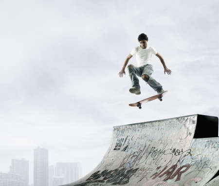 Young male skateboarder in mid air above a ramp