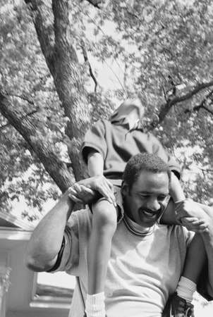 Mid adult man carrying a young boy on his shoulders