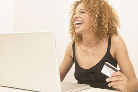 Businesswoman smiling sitting at a desk using a laptop