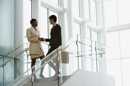 Businesswomen shaking hands on stairway