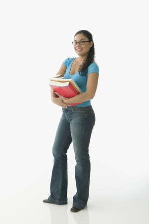 Teen girl holding school text books LANG_EVOIMAGES