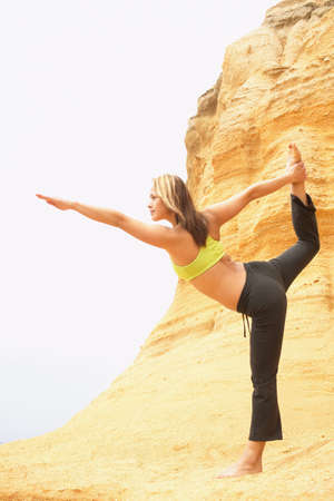 Young woman standing on a rock performing stretching exercises